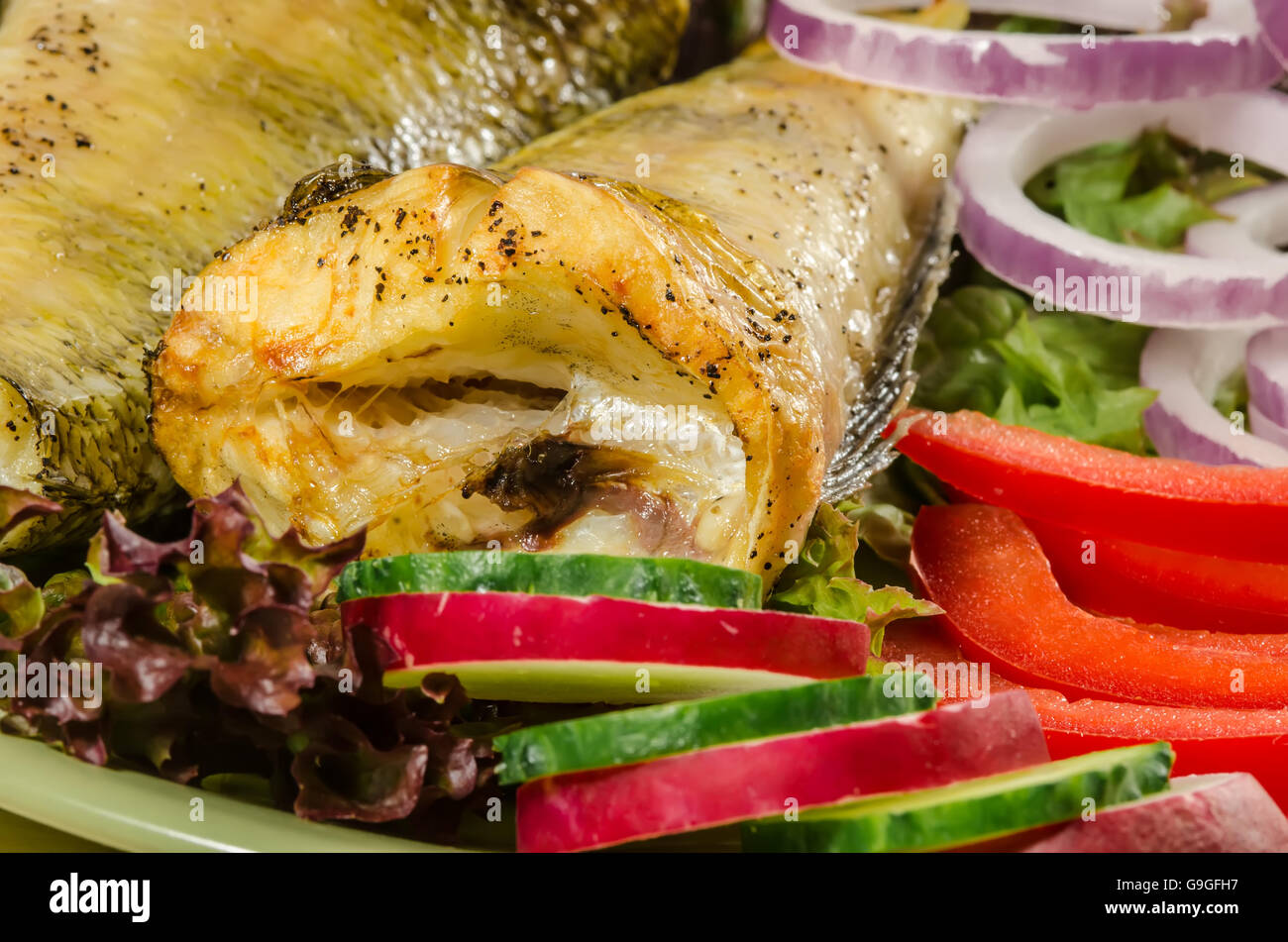 Baked shad with vegatables at dish close up - Stock Image