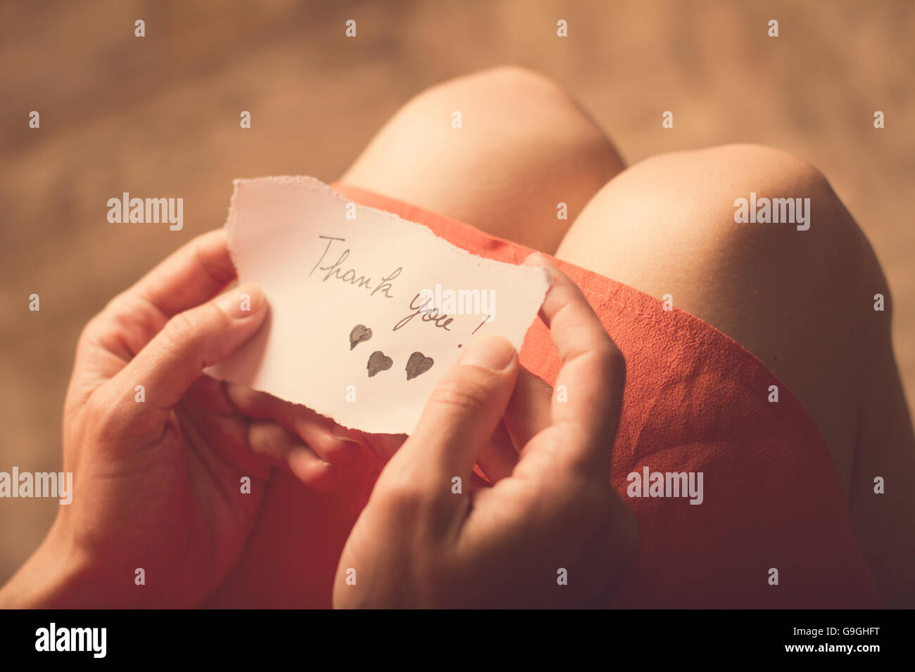 Top view of a woman with pink dress holding a thank you note in her hand Stock Photo