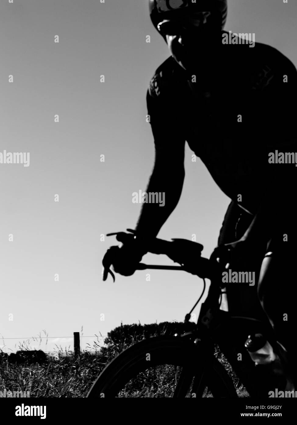 Cyclist closeup gritty image blurred in motion as competitive effort is applied to pedaling. - Stock Image