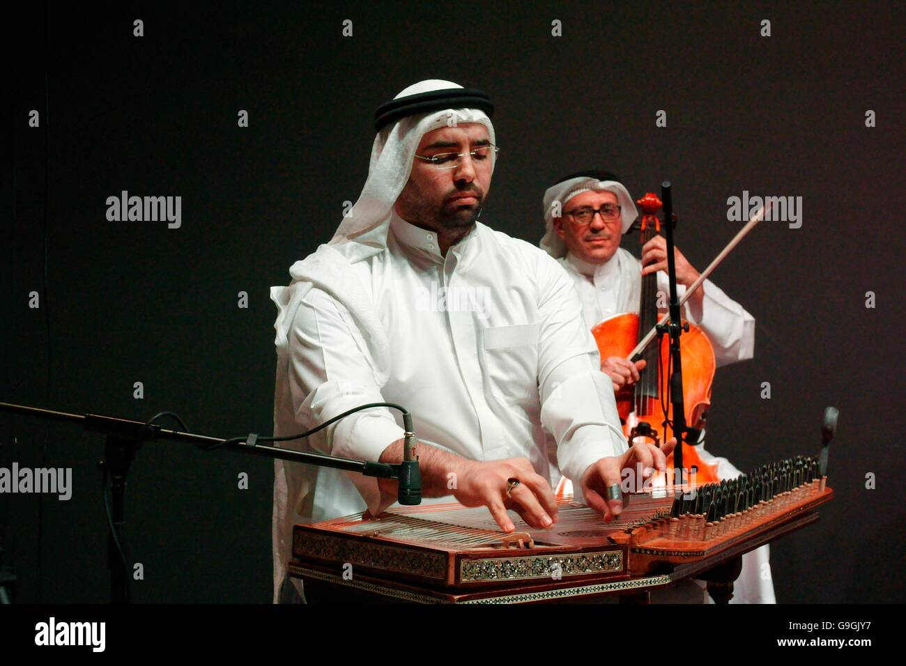 Musician of the Mohammed bin Faris Ensemble plays qunan zither at traditional sawt music concert in Al Khalifa Centre, Stock Photo