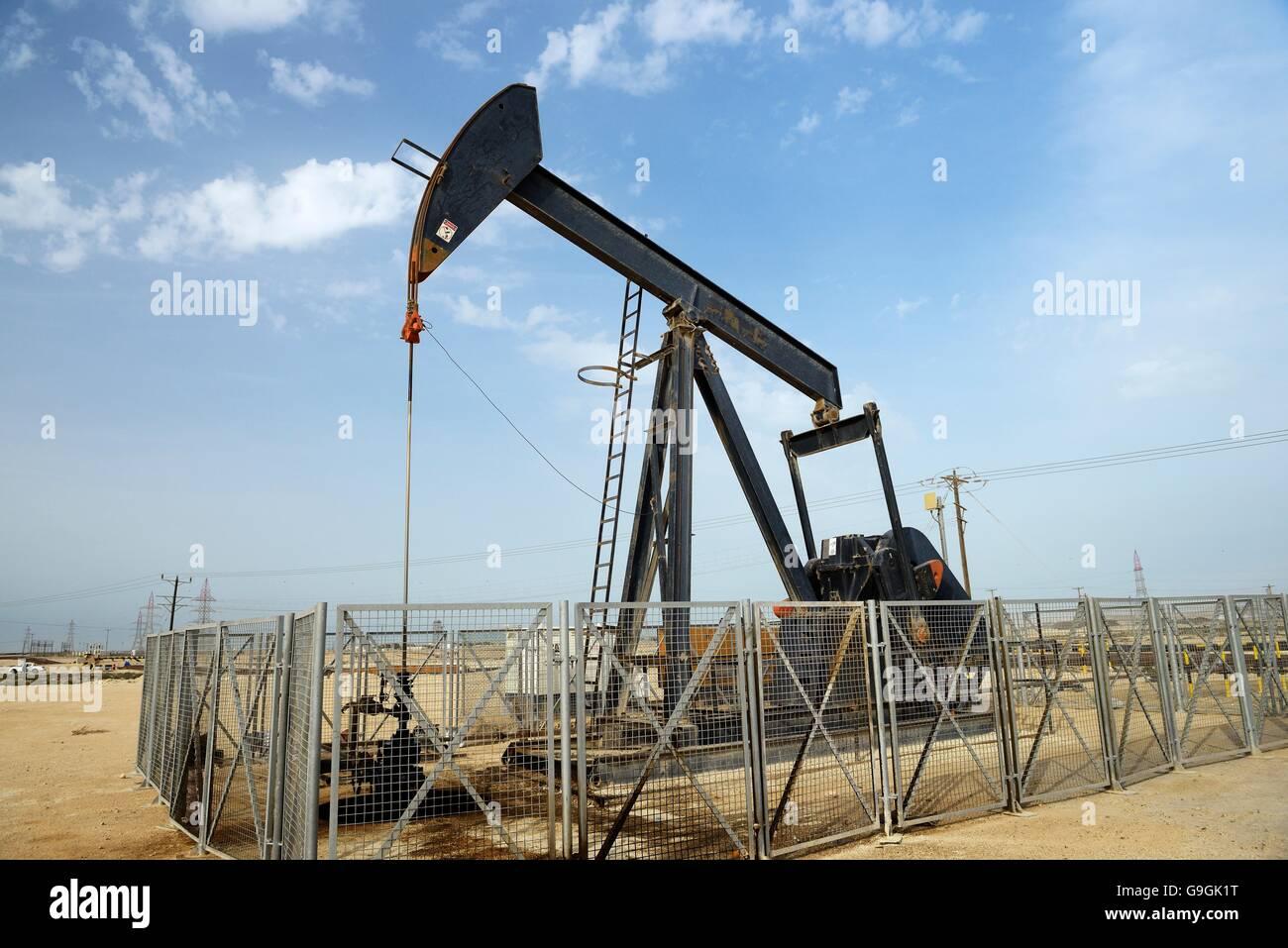 Pumpjack aka oil horse, nodding donkey, oil jack, beam pump raises crude oil in the Bahrain desert at Sakhir on - Stock Image
