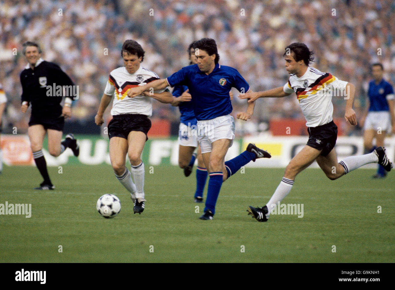 Italy's Carlo Ancelotti (c) tries to burst between West Germany's Lothar Matthaus (l) and Thomas Berthold (r) Stock Photo