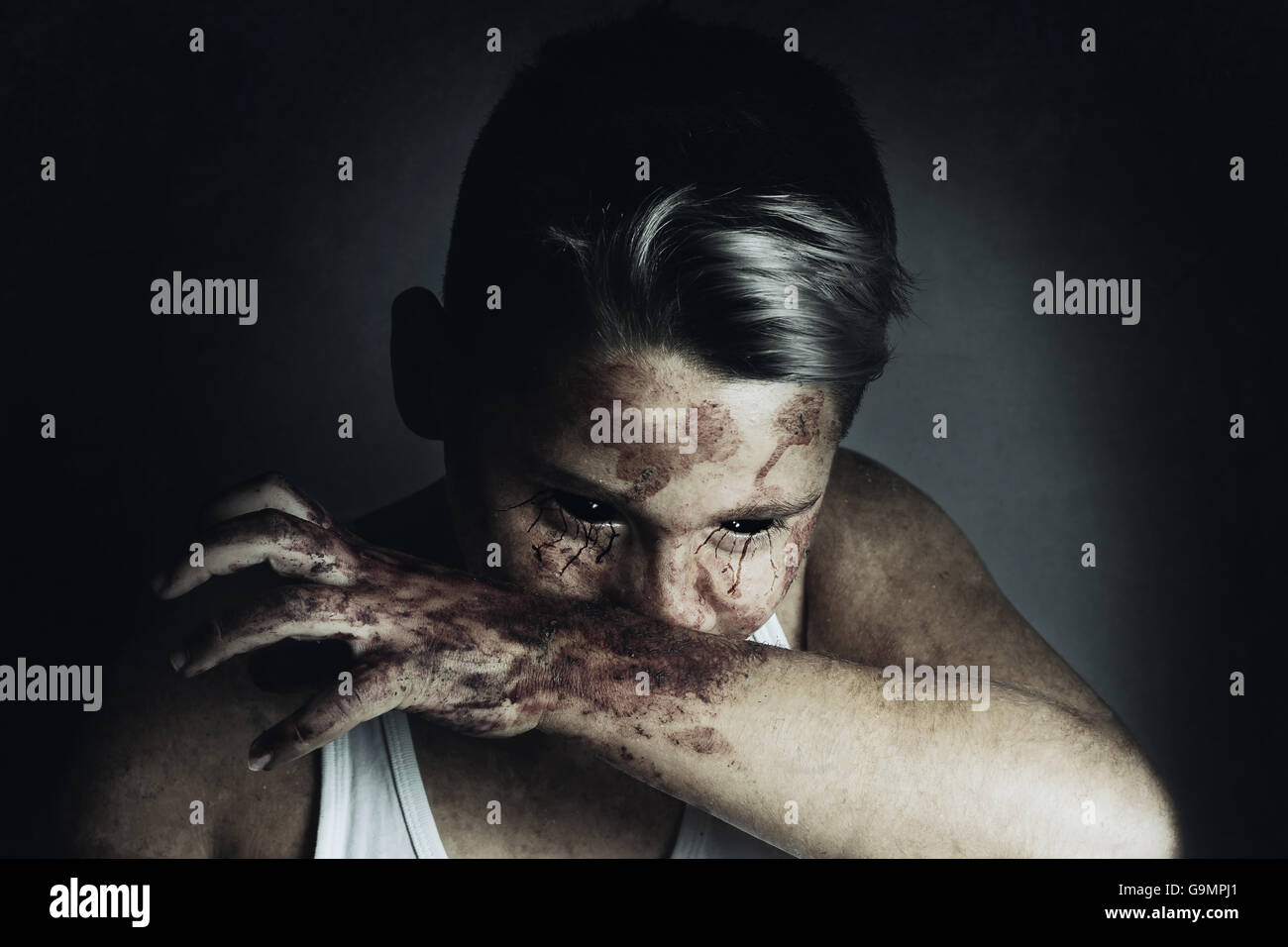 portrait of angry bloodsucker who wipe the mouth with bloody hand - Stock Image