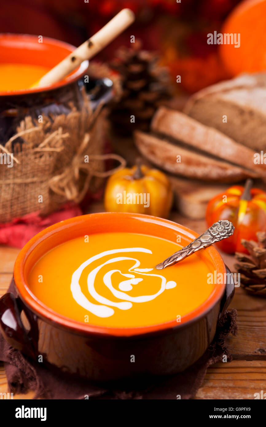 A bowl of homemade creamy pumpkin soup on a rustic table with autumn decorations. - Stock Image