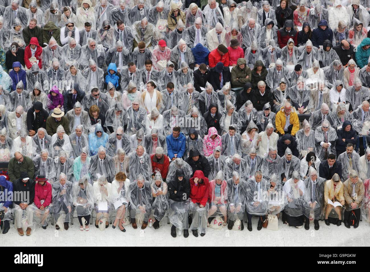 Guests wear ponchos to shelter from the rain during a service to mark the 100th anniversary of the start of the - Stock Image