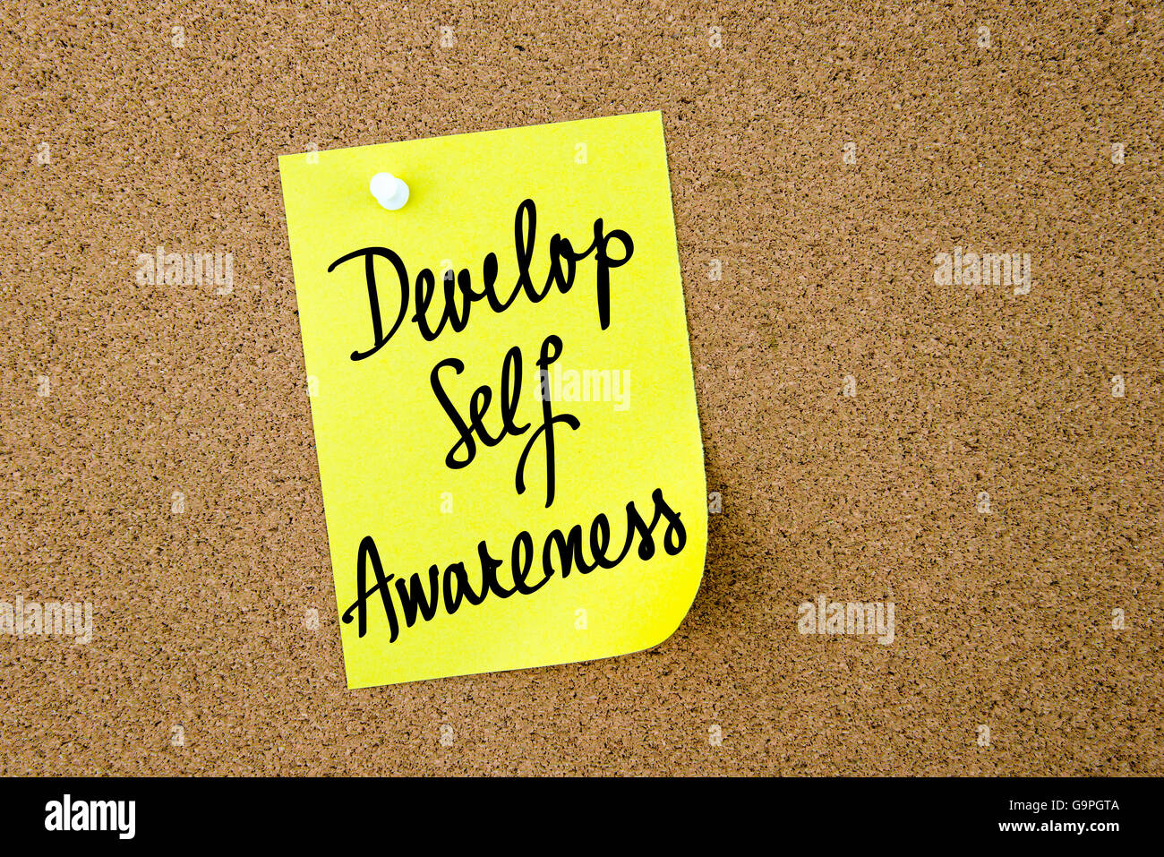 Develop Self Awareness written on yellow paper note pinned on cork board with white thumbtacks, copy space available - Stock Image