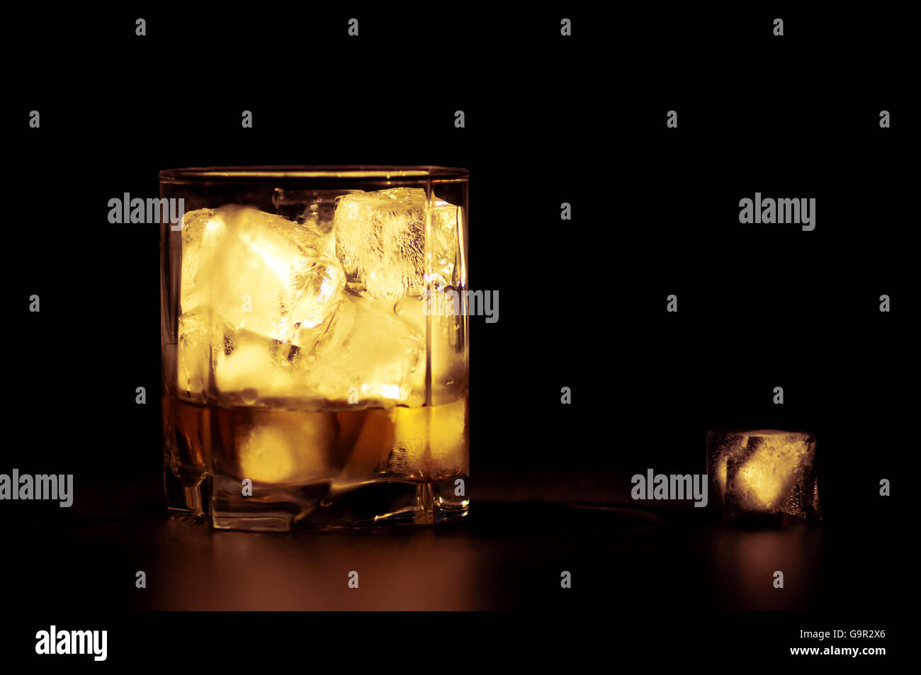 Whiskey with ice cubes in warm tones - Stock Image