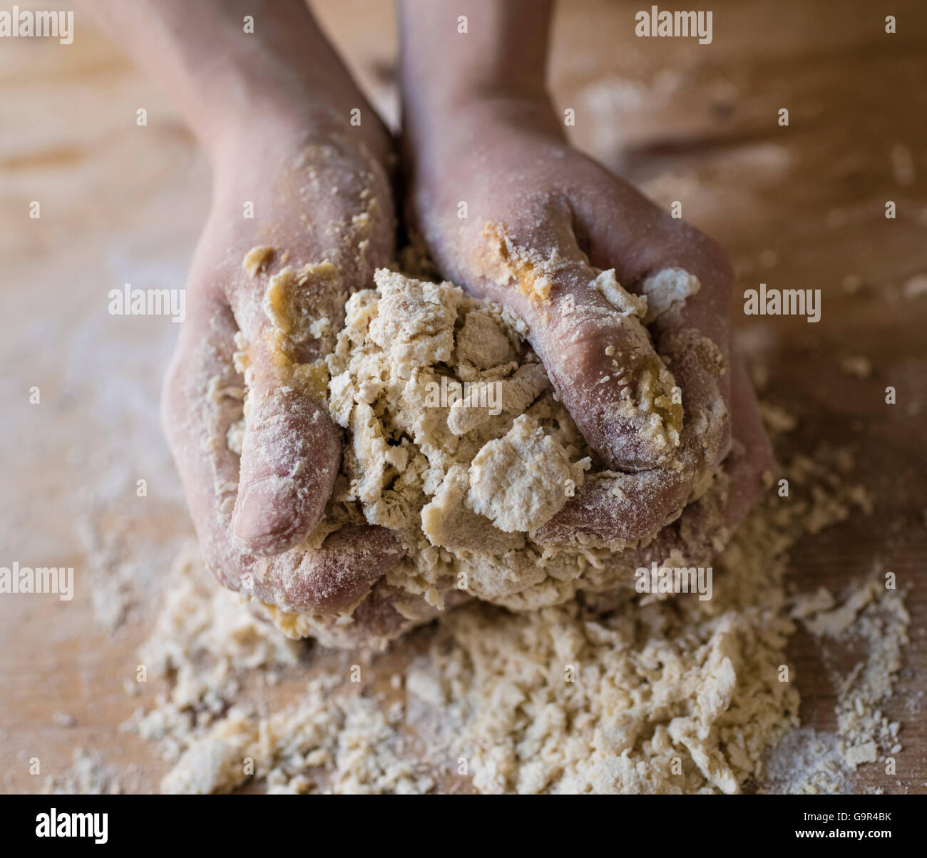 Close-up of two strong hands of a baker that are manually kneading dough on a rough, wooden kitchen table - Stock Image