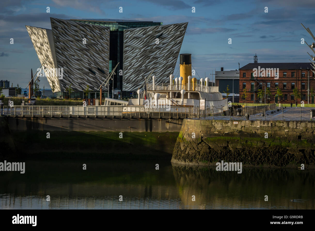The Titanic Belfast Visitor Experience Centre with SS Nomadic in the foreground - Stock Image
