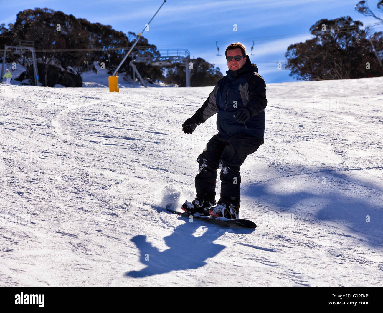 Happy snowboarder slides down the track in Snowy Mountains ski resort of Perisher Valley, kosciuszko national park. - Stock Image