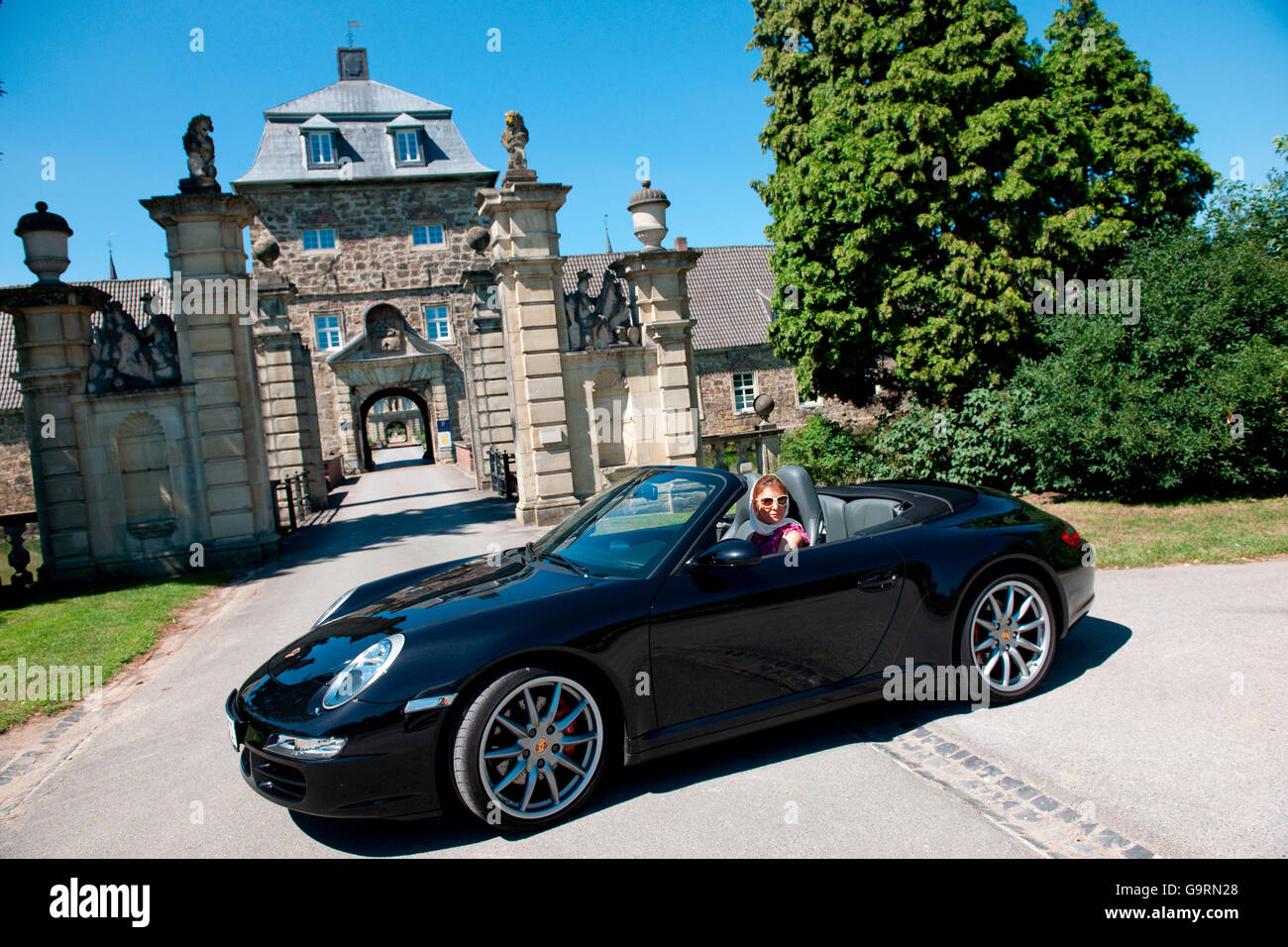 stylish woman and Porsche 911 in front of castle, 911 carrera, 4S, convertible car, sportscar, luxurious - Stock Image