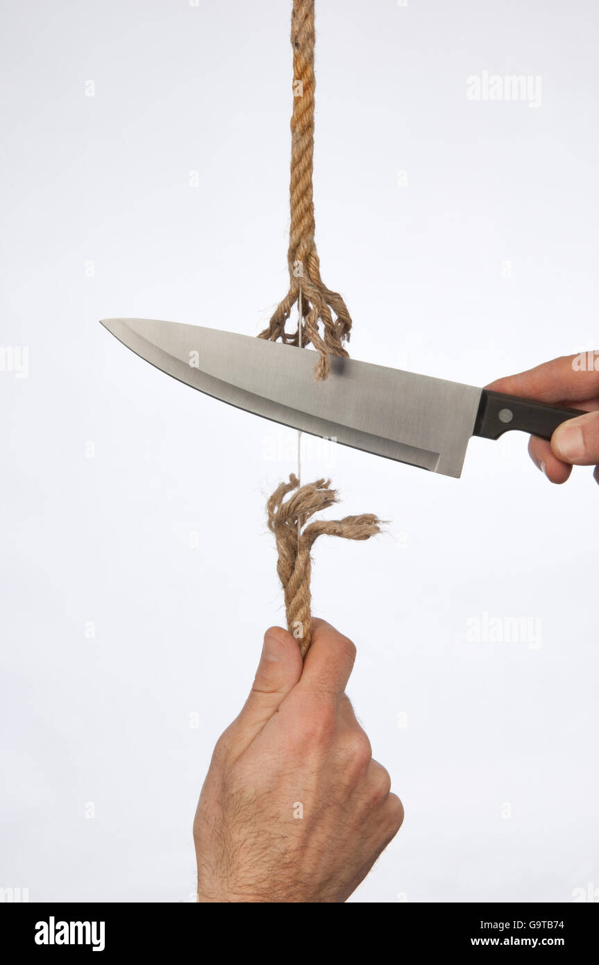 Hand holds a rope, a knife cuts the same string - Stock Image
