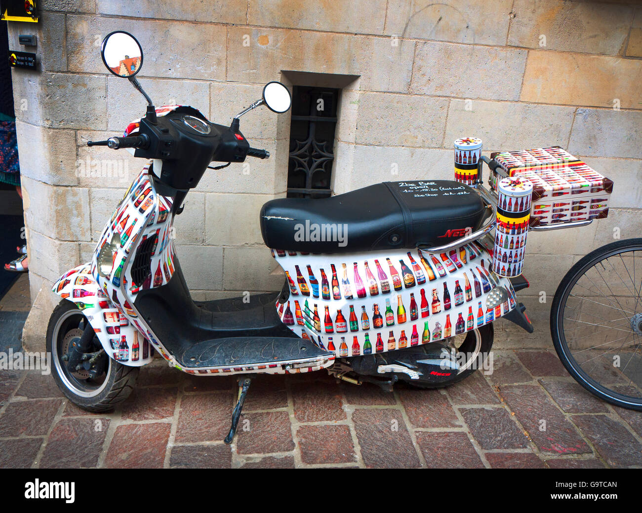 Promotional scooter decorated with pictures of beer bottles in Bruges, Belgium. - Stock Image