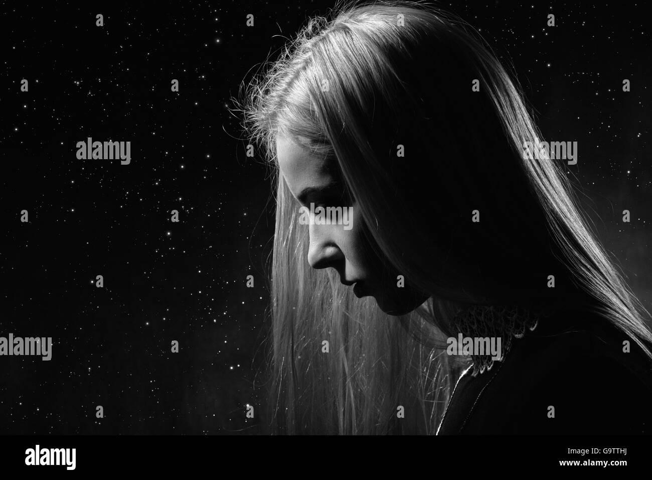 sad pensive girl profile on stars sky background, monochrome image - Stock Image