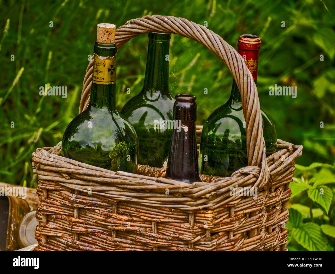 A still life of four old empty wine bottles in a basket - Stock Image