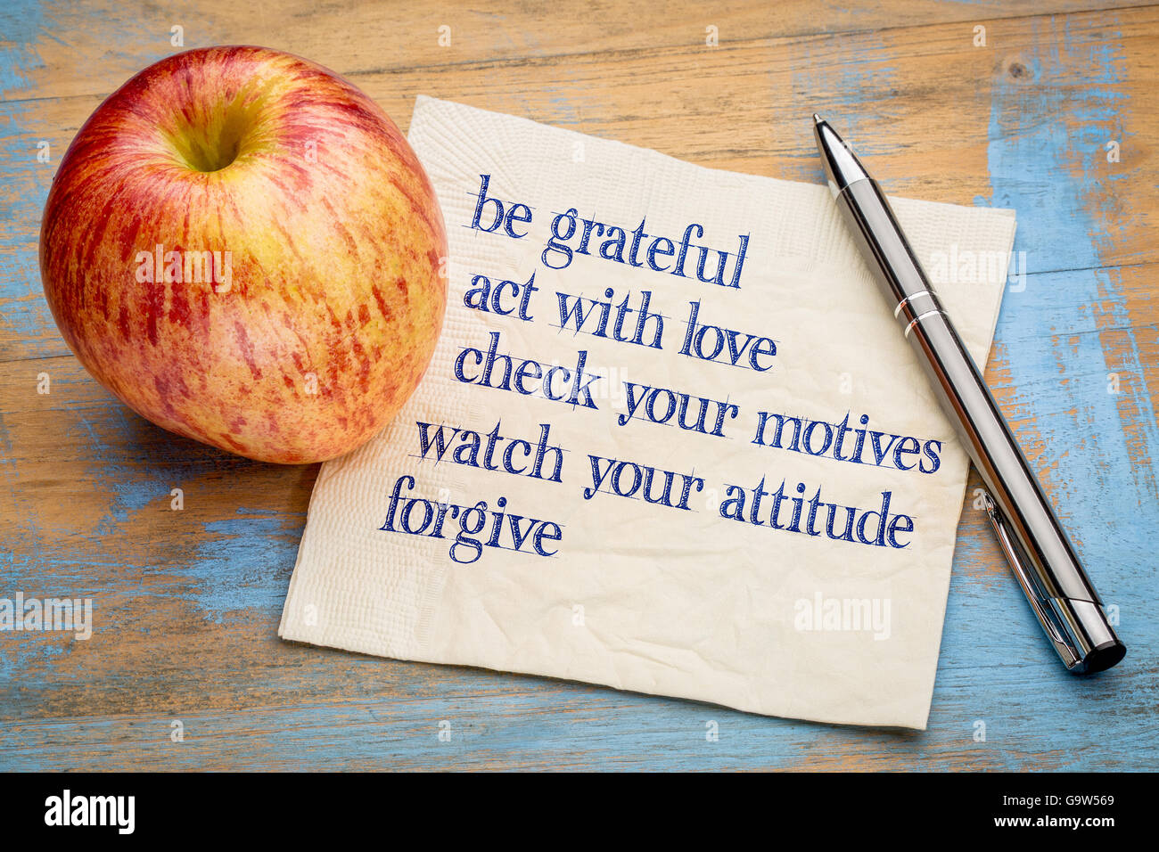 be grateful and other inspirational phrases - handwriting on a napkin with a fresh apple - Stock Image