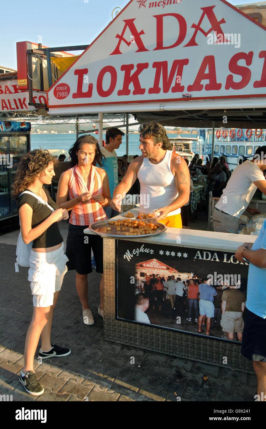 woman tasting sweets at turkish market, Ayvalik, Cunda, Balikesir, Turkey, Asia / Ayvalik - Stock Image
