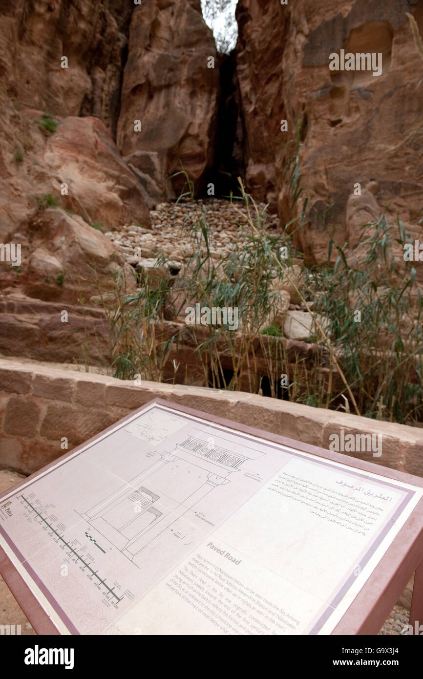 ancient nabataean dam in Siq against flood, information plate for paved road, Petra Archaeological Park, Petra, Stock Photo