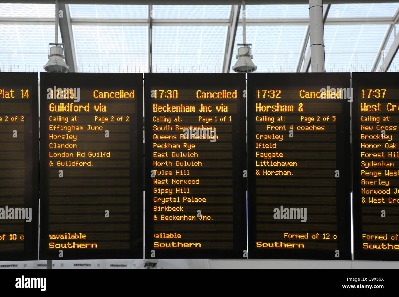 Southern train departure board at London Bridge station shows three canceled rush-hour  trains on adjacent panels. - Stock Image