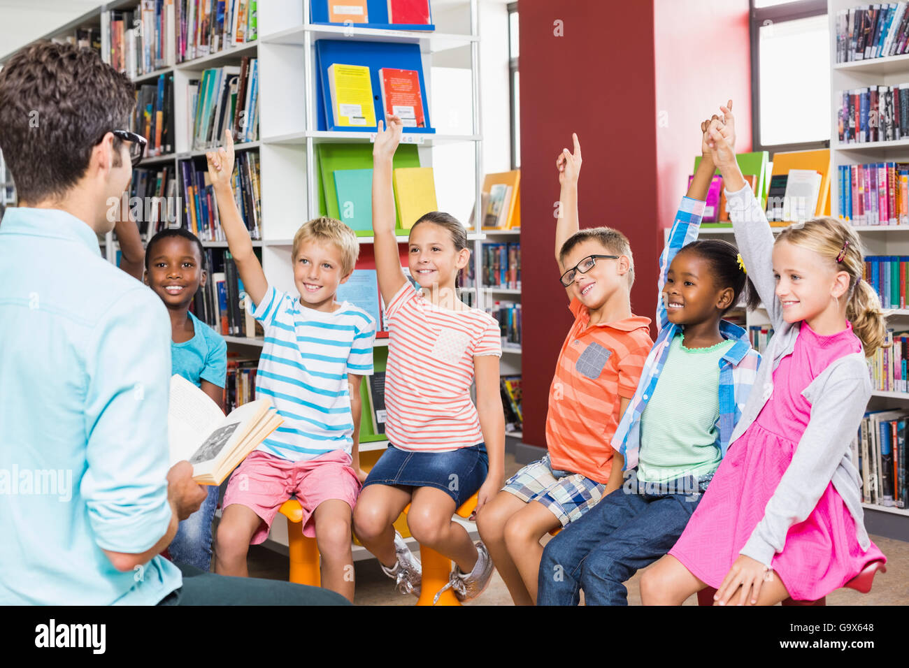 Kids raising their hands in library Stock Photo