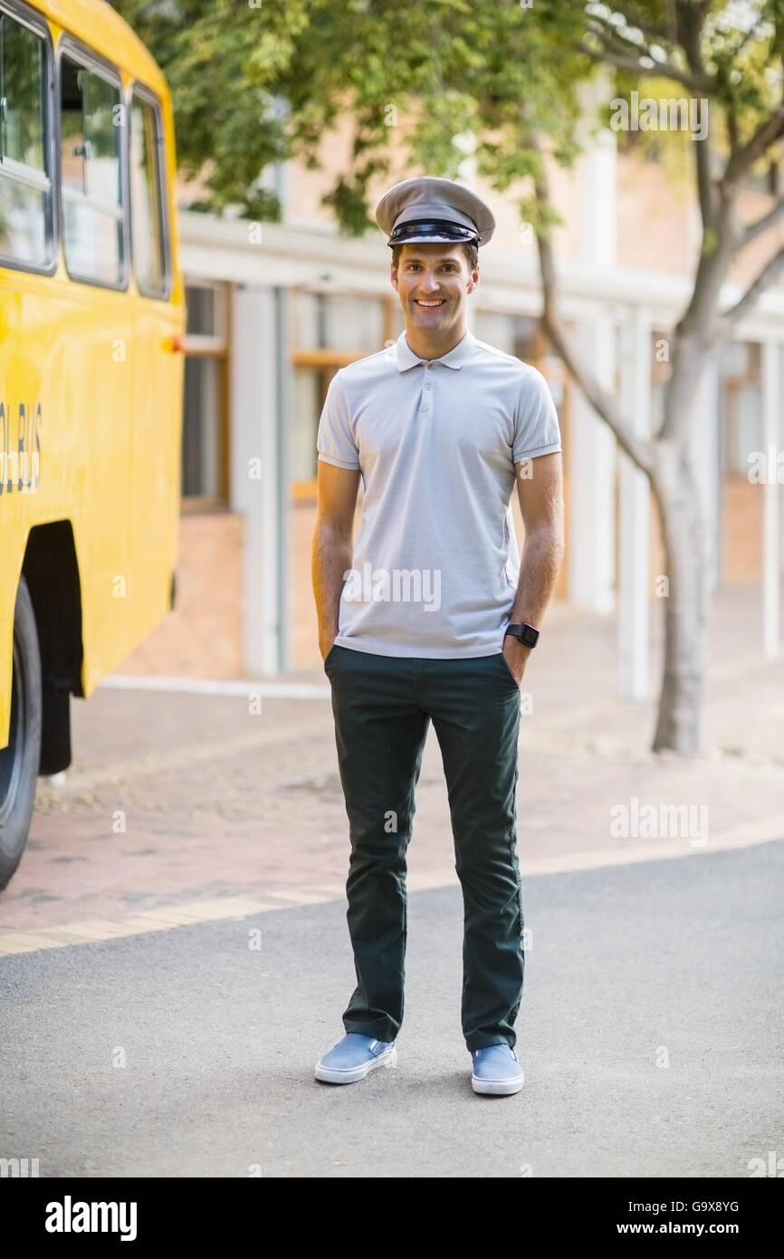 f8f083a75245 Smiling bus driver standing with hands in pocket in front of bus - Stock  Image