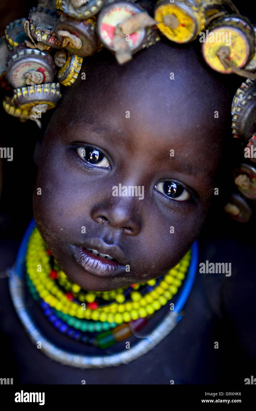 Dassanech baby with her headdress made from bottlecaps, Lower Omo Valley. Ethiopia, November 2014 - Stock Image