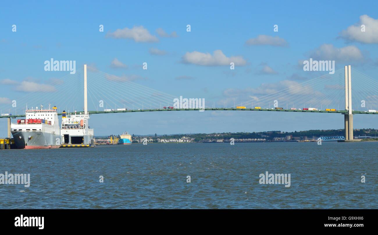 Cargo ships moored on the Thames underneath the M25 Dartford Crossing Queen Elizabeth II bridge - Stock Image