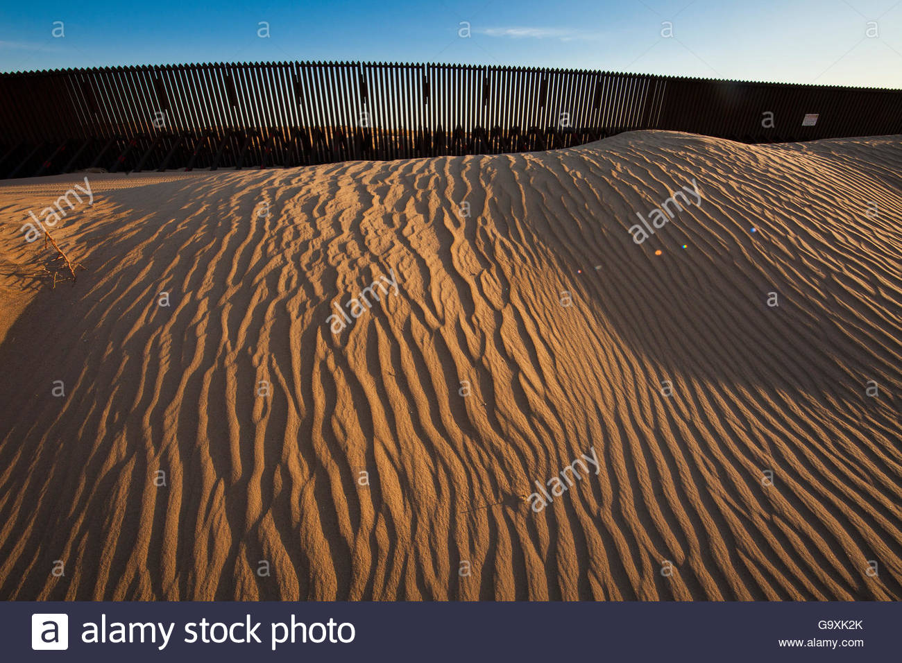 US-Mexico border wall with Algodones Sand Dunes, one of North Americas largest dunefields, California, USA. March - Stock Image