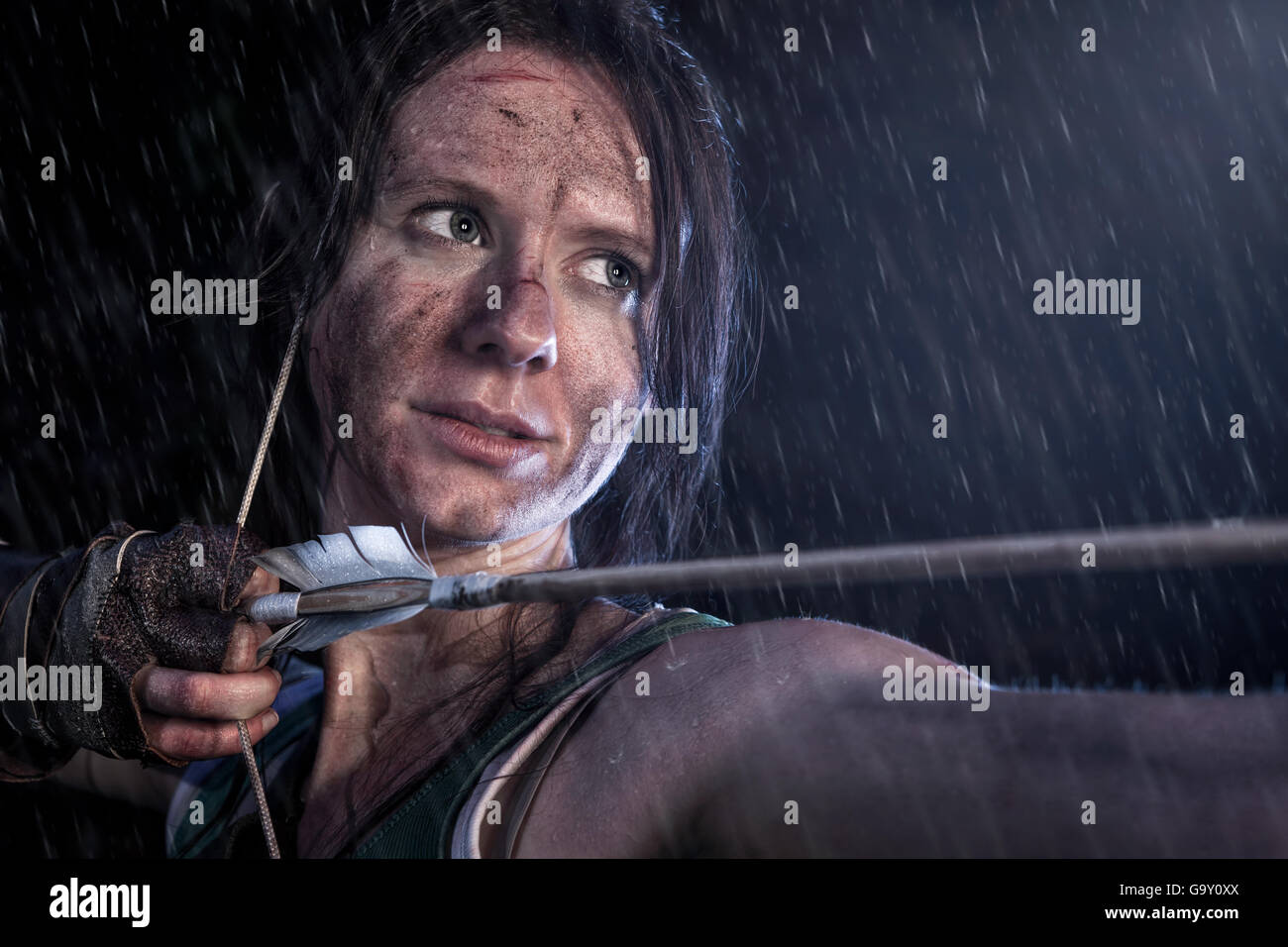 Rise of the Tomb Raider. Woman dressed up as Lara Croft stands in the rain, aiming with a bow and pulling the bowstring - Stock Image