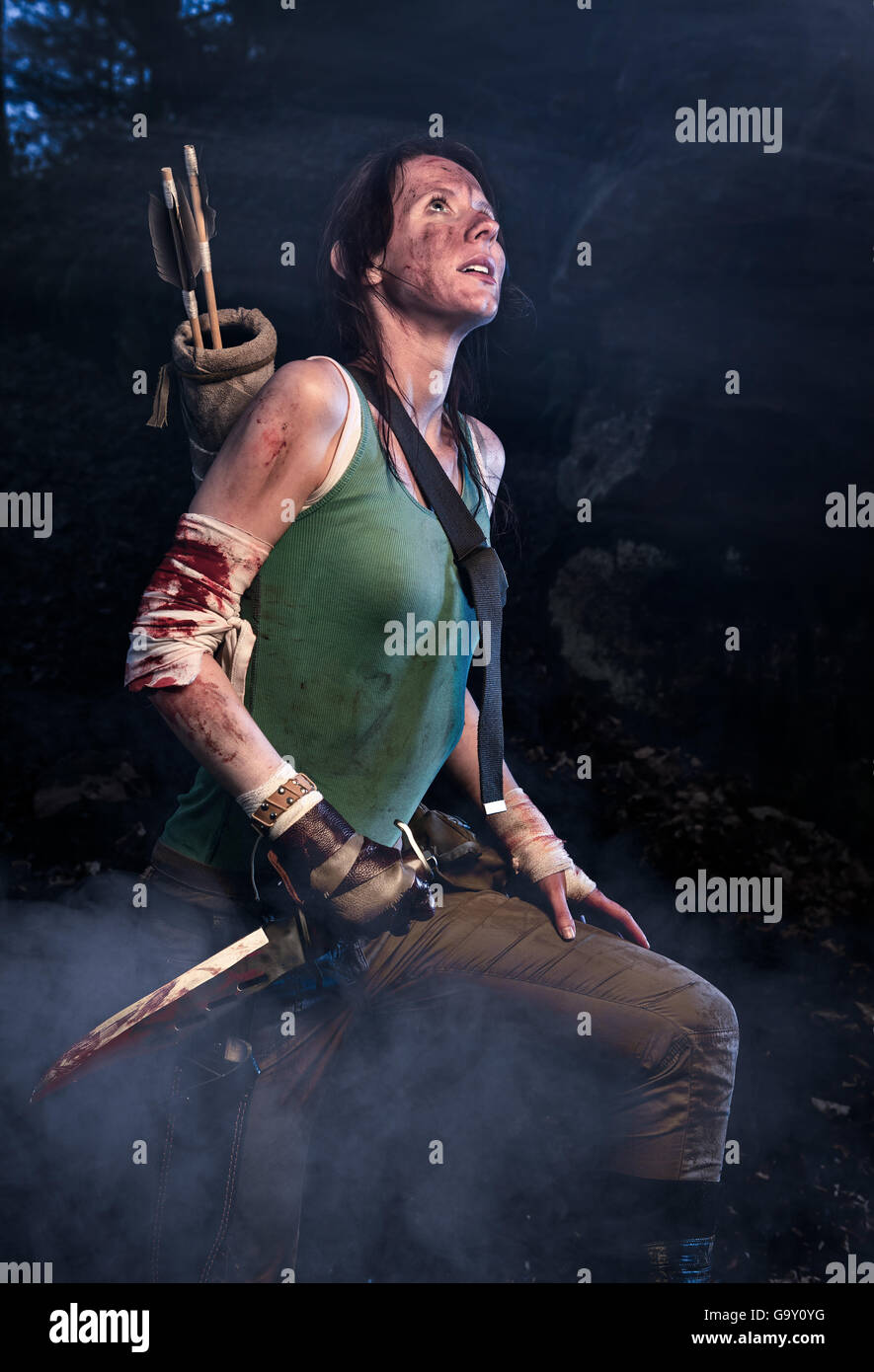 Rise of the Tomb Raider. Woman dressed up as Lara Croft stands next to the caves, holding a knife in the hand. - Stock Image