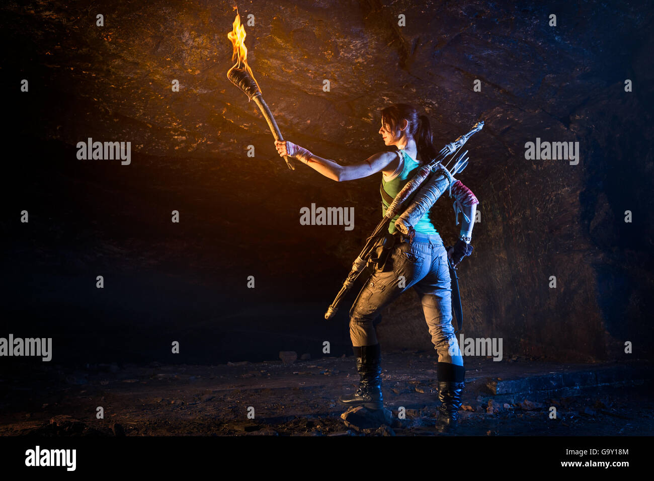 Tomb Raider. Lara Croft-like character exploring caves holding torch in one hand, knife in the other. Wears bow - Stock Image