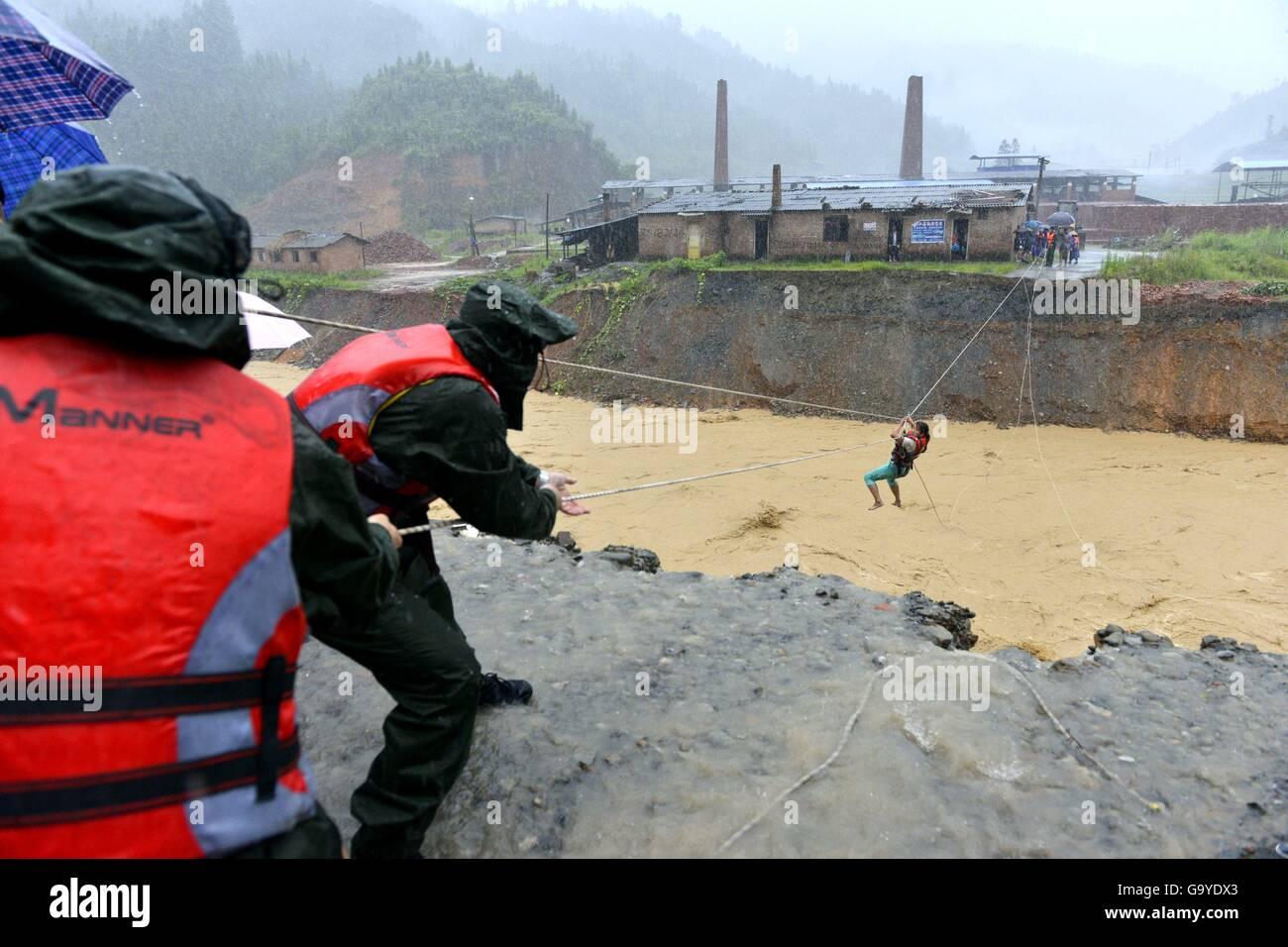 Qiandongnan, China's Guizhou Province. 2nd July, 2016. Rescuers help evacuate a woman in Pingyong Town of Rongjiang - Stock Image