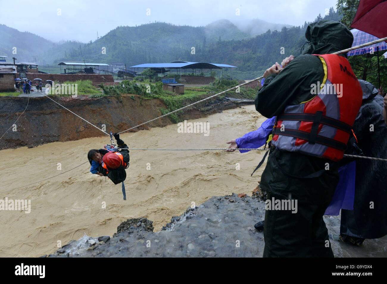 Qiandongnan, China's Guizhou Province. 2nd July, 2016. Rescuers help evacuate a kid in Pingyong Town of Rongjiang - Stock Image