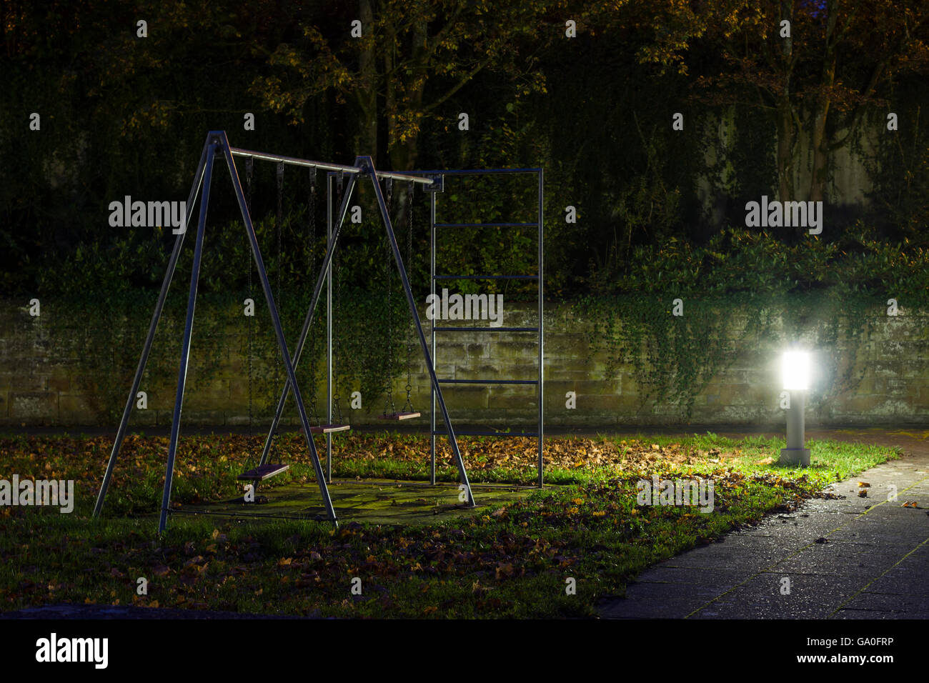 an empty playground with metal swings at night with fog and creepy atmosphere - Stock Image