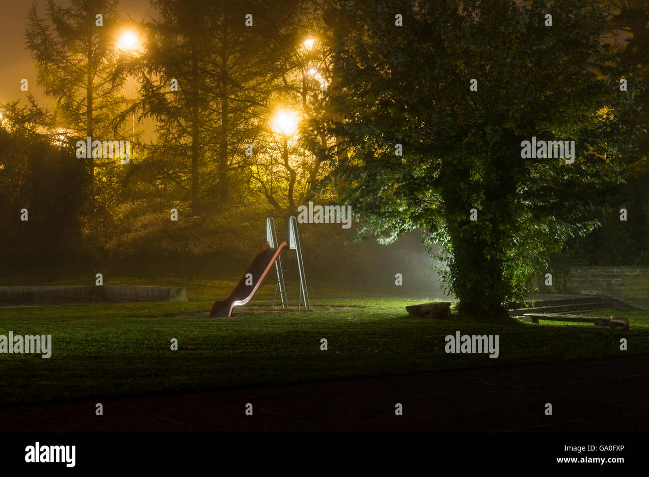 an empty playground with a red slide at night with fog and creepy atmosphere - Stock Image