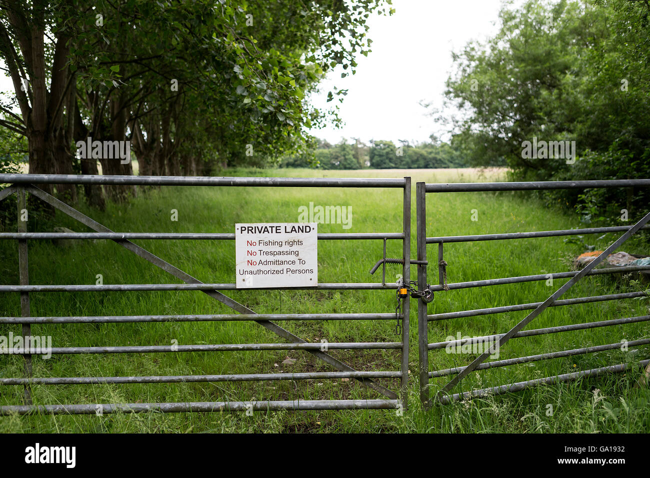Locked galvanised gates leading to a tree-lined field and a sign stating that this is private land Stock Photo