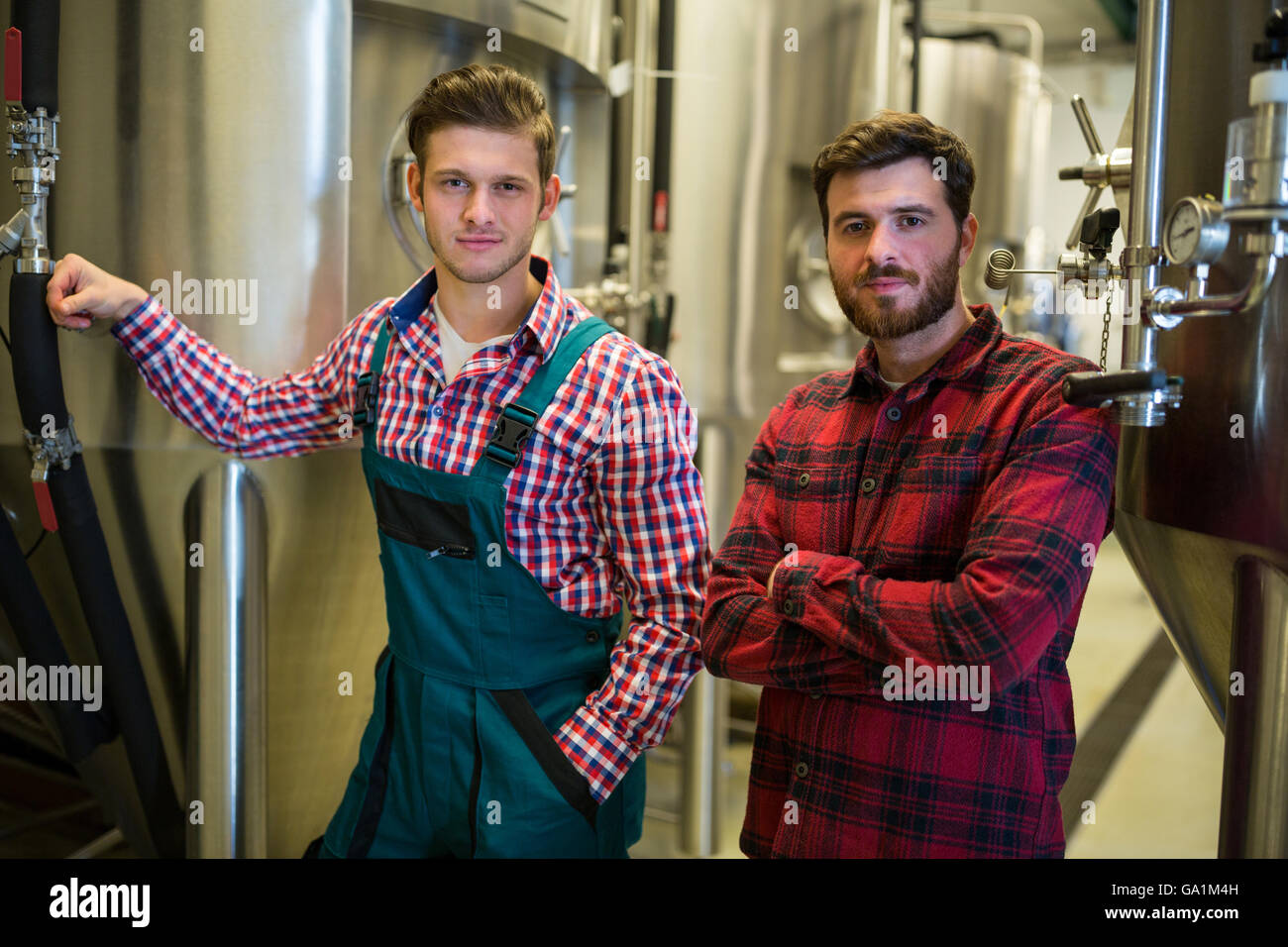 Brewers with arms crossed at brewery - Stock Image