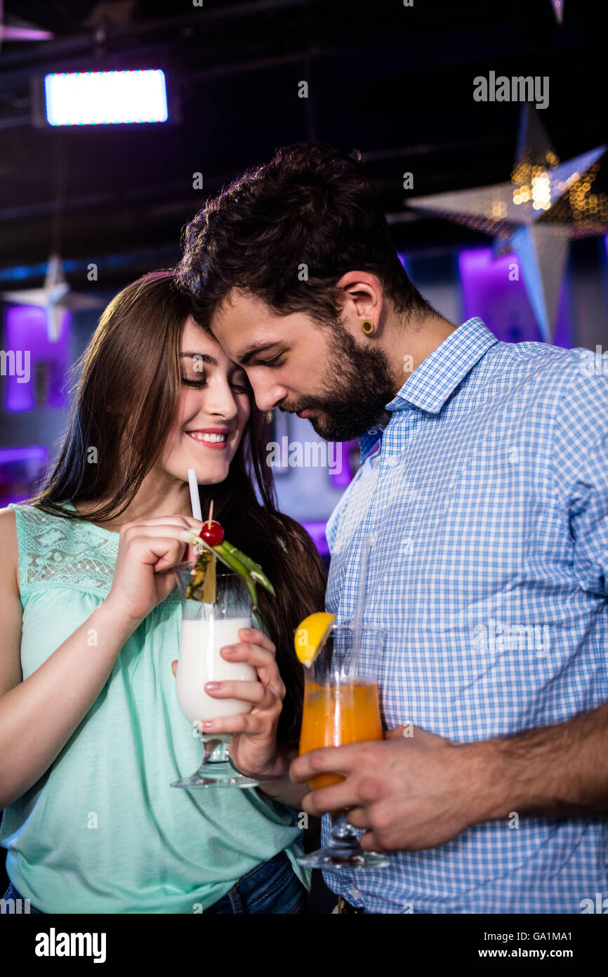 Couple embracing each other at bar counter while having cocktail - Stock Image