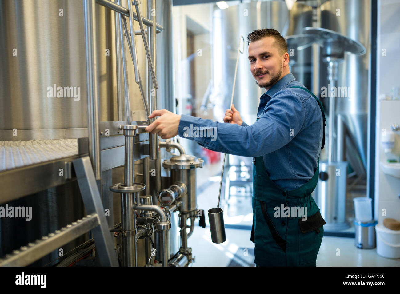 Brewer working at brewery - Stock Image