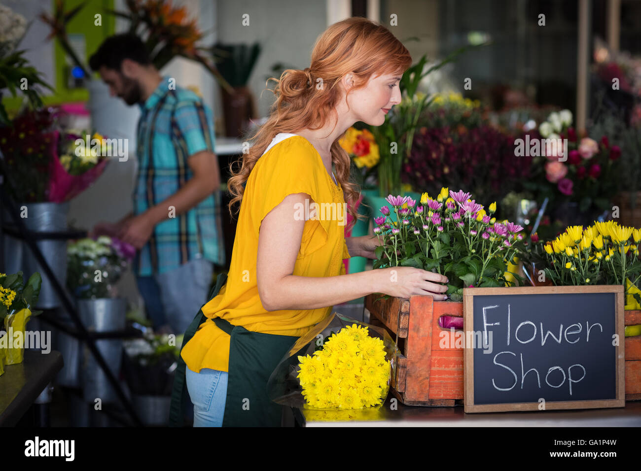 Female florist arranging flower bouquet - Stock Image