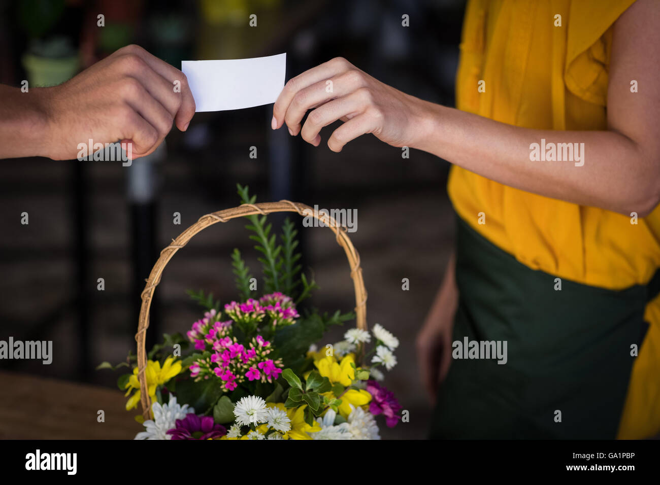 Female florist giving visiting card to customer - Stock Image