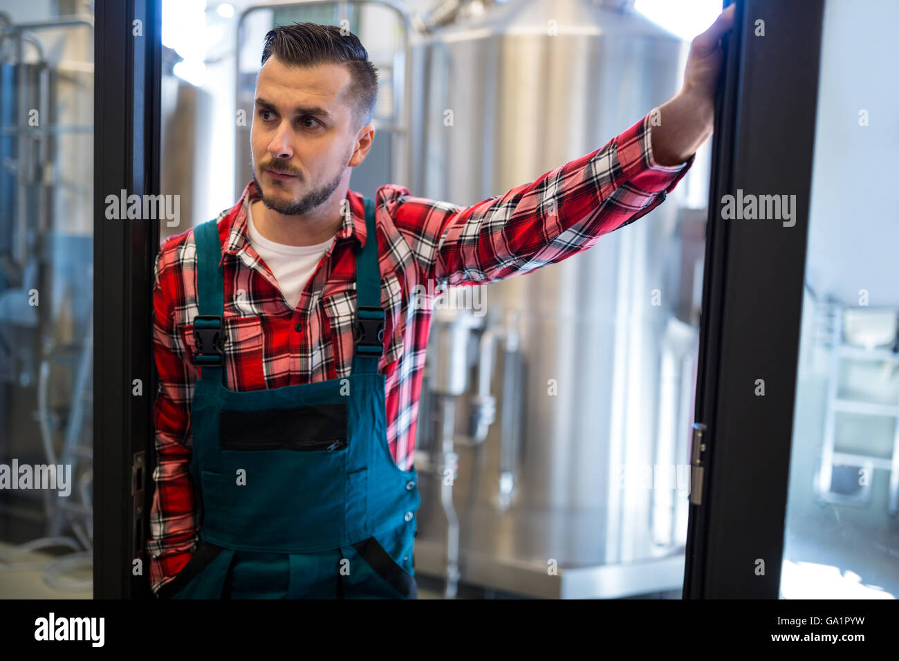 Brewer standing at brewery - Stock Image