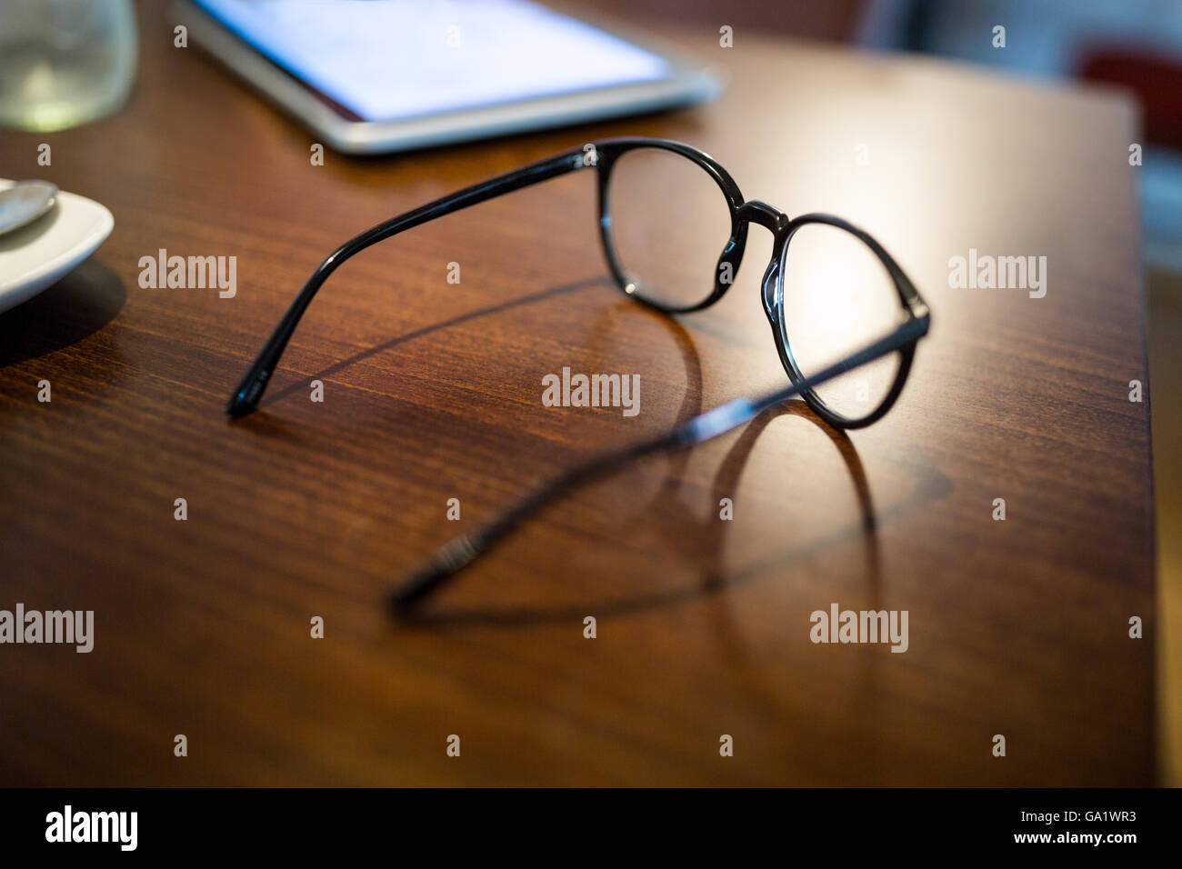 Close-up of spectacle and mobile phone on wooden table - Stock Image