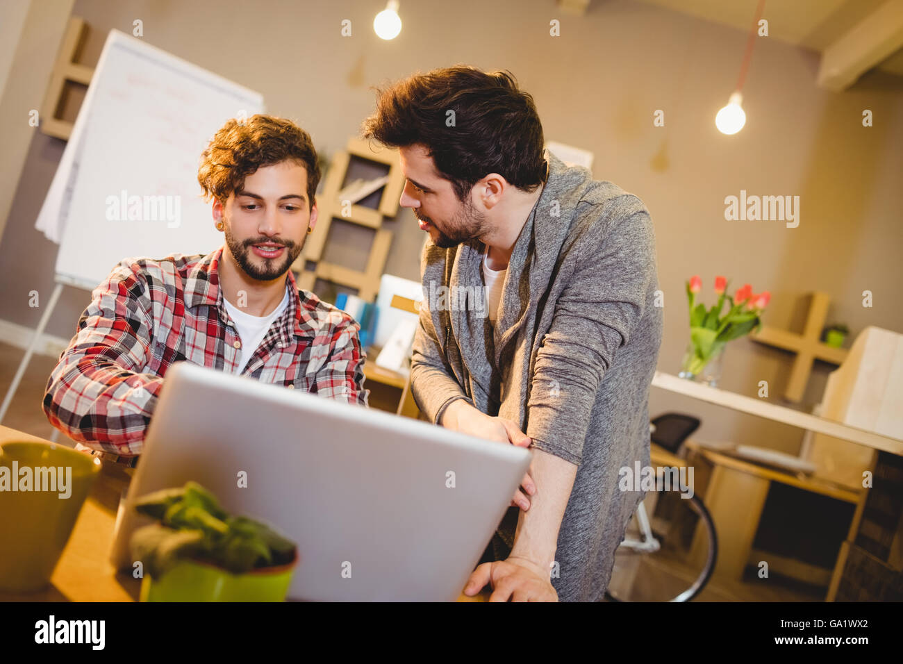 Graphic designer using laptop with his coworker - Stock Image