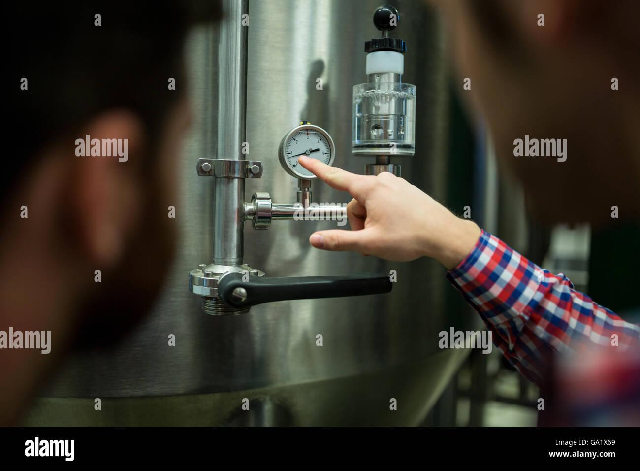 Maintenance workers examining pressure - Stock Image
