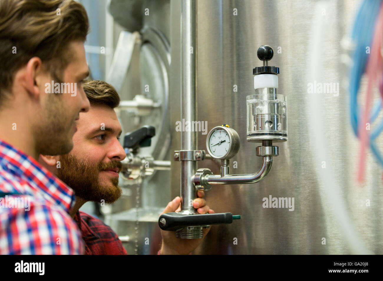 Maintenance workers examining pressure - Stock Image