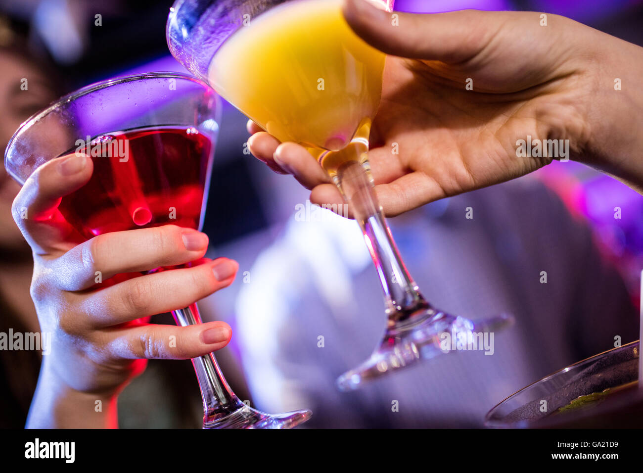 Friends toasting cocktail at bar counter - Stock Image