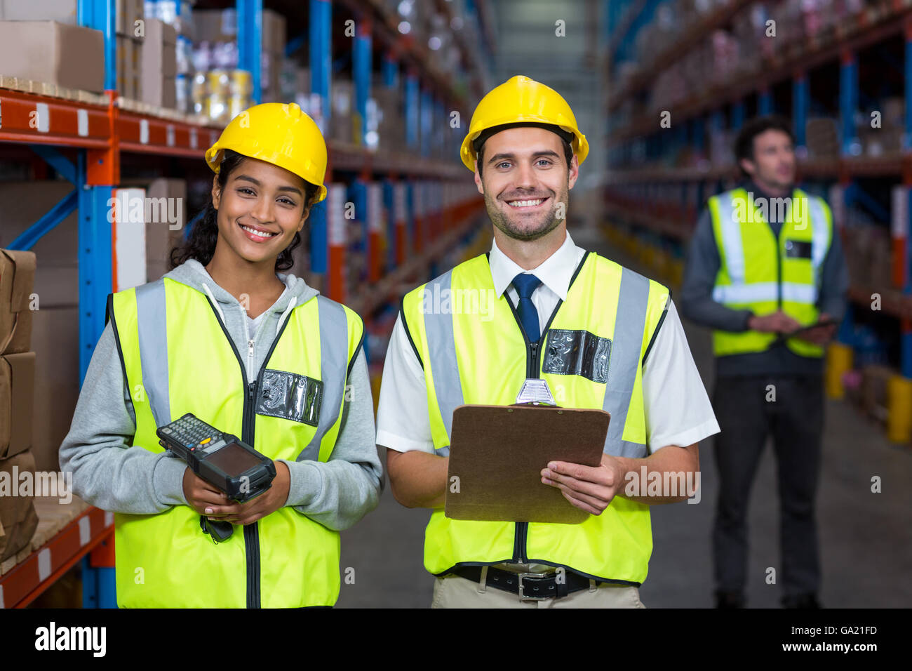 Smiling worker wearing yellow safety vest looking at camera - Stock Image