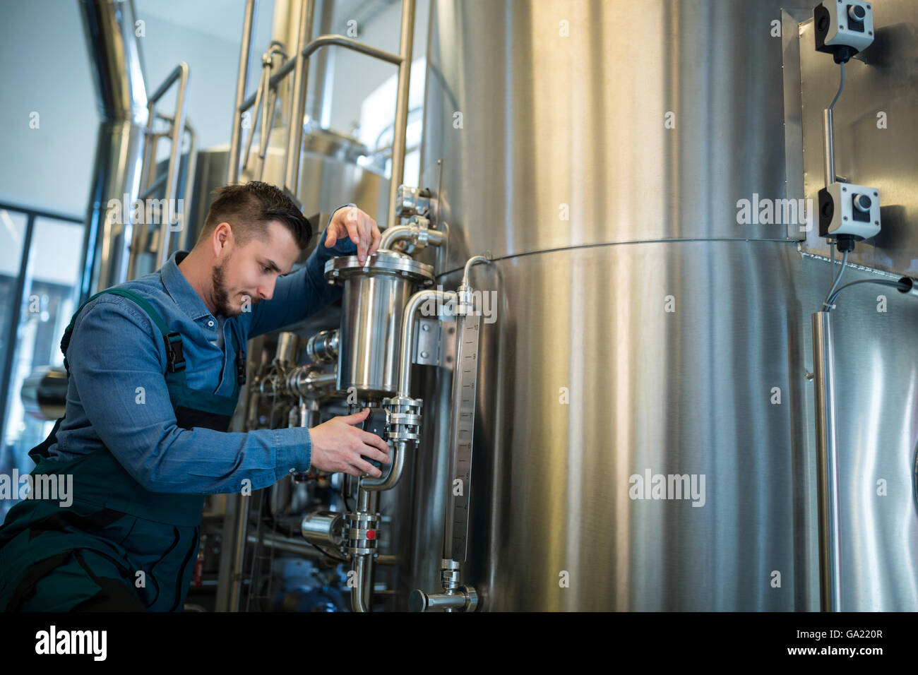 Brewer checking pressure at brewery - Stock Image