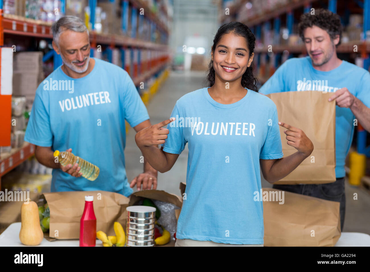 Happy volunteer showing her tee-shirt to the camera in front of her team - Stock Image